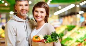 Image of happy couple with healthy products looking at camera in supermarket